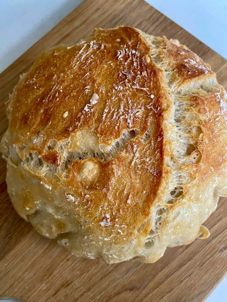 No knead bread full load baked and on a chopping board